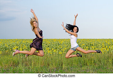Acrobatic women leaping in unison with their legs high and...