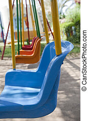 Closeup of swings in a playground - Closeup of colourful...