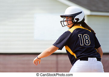 Young teen girl playing softball in organized game