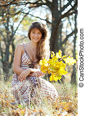 girl with oak leaves posy in autumn park