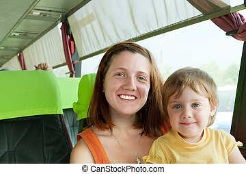 traveling family - woman with her child in bus cabin