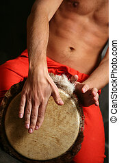 Drummer - Man playing the djembe nigerian drum in studio