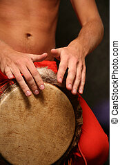 Drummer - Man playing the djembe (nigerian drum) in studio