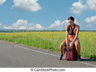 Dejected woman waiting for a lift seated on a large suitcase...