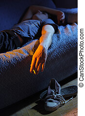 Smoking a joint at home - Young man lying on the couch...