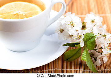 Tea with flower - Tea in white cup with lemon and cherry...