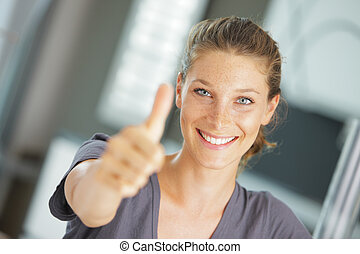 Close-up of a happy young woman showing thumbs up sign -...