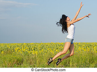 Woman jumping for joy - Woman in sexy denim shorts anf...