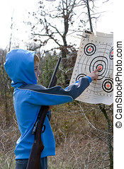 Boy checking target - Boy checking his target while holding...