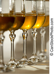Glasses for wine with white wine on a white background. One...