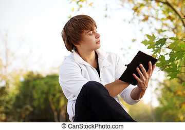 portrait of young man read the book, outdoor autumn
