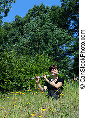 Ambiance - Flute player, dressed in black, sits on a grassy...