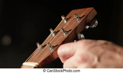 guitar tuning keys - Close up shot of a mans hand turning a...