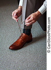 Tying shoes - A young man tying elegant shoes indoors