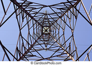 Transmission tower as seen from below towards a blue sky