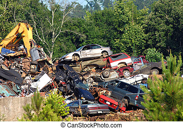 Auto Graveyard - A pile of wrecked cars and auto bodies are...