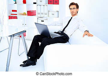 modern office - Handsome businessman is working on a laptop...