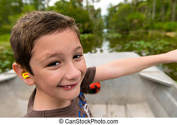 Boy in the everglades - Young boy enjoys a boat ride in the...