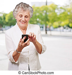 Senior woman using cellphone, outdoor