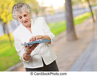 Senior woman using ipad, outdoor