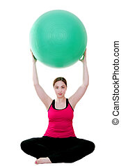 pilates exercises - young woman holding pilates ball over...