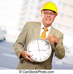 Portrait Of A Senior Man Holding A Wall Watch, Outdoor