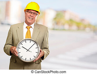 Portrait Of A Senior Man Holding A Wall Watch, Background