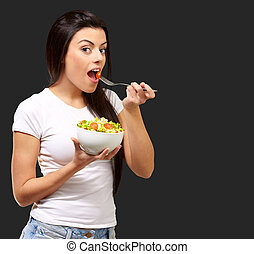 Young Girl Eating Salad From Bowl Isolated On Black...