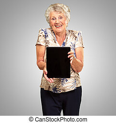 Portrait Of A Senior Woman Holding A Digital Tablet On gray...