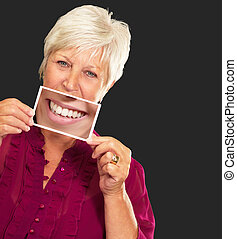 Senior Woman With Magnifying Glass Showing Teeth On Black...