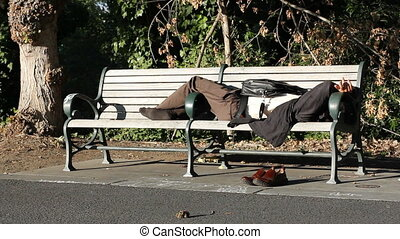 man sleeps on bench - This is a static shot of a man...