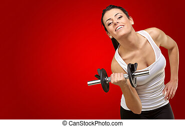 Young woman holding dumbells on red background
