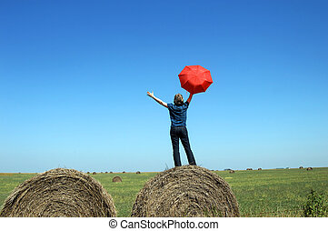 Embracing her state - Woman stands on top of round hay bales...