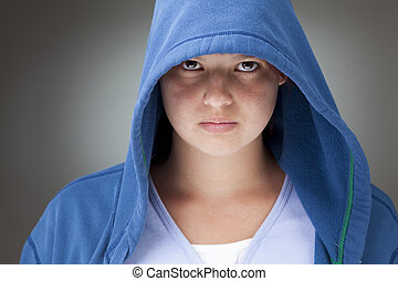 Girl in a hooded jacket - Studio portrait of a serious...