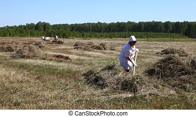 Peasants On the farm - Man and woman gather hay in a...