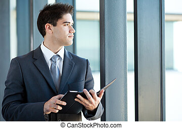thoughtful businessman with tablet computer