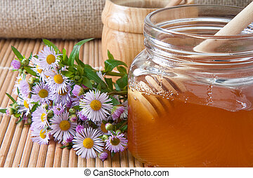 honey, flowers and pot on straw table