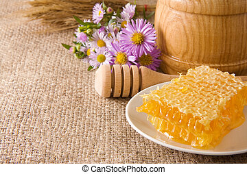 honeycomb, flowers and honey in pot on sack