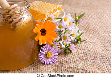 honeycomb, flowers and honey in pot