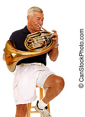 French Horn Player - Senior man playing his french horn...