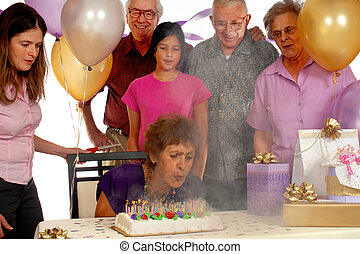 Cake on Fire - Senior woman, surrounded by family an friend,...