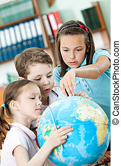Classmates help to each other to find something at the globe...