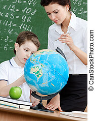 Geography teacher explains something to the pupil