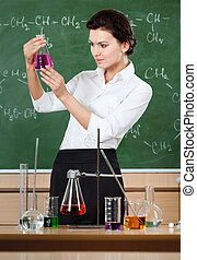 Smiley chemistry teacher examines conical flask with pink...