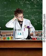 Mad professor scratches his head working in his laboratory