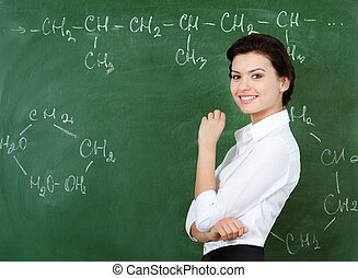 Smiley teacher hands chalk standing at the blackboard where...