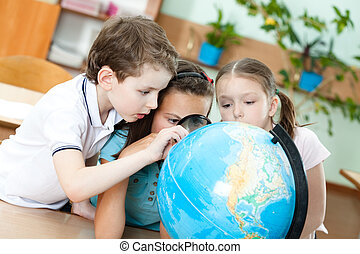 Three friends examine a school globe - Three friends examine...