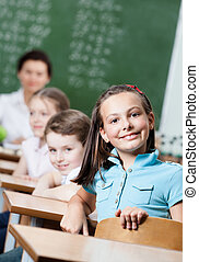 Smiley schoolgirl sits at the desk