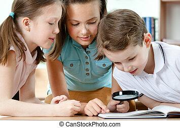 Pupils examine something through the loupe - Pupils examine...