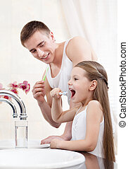 Father teachers his daughter to clean teeth